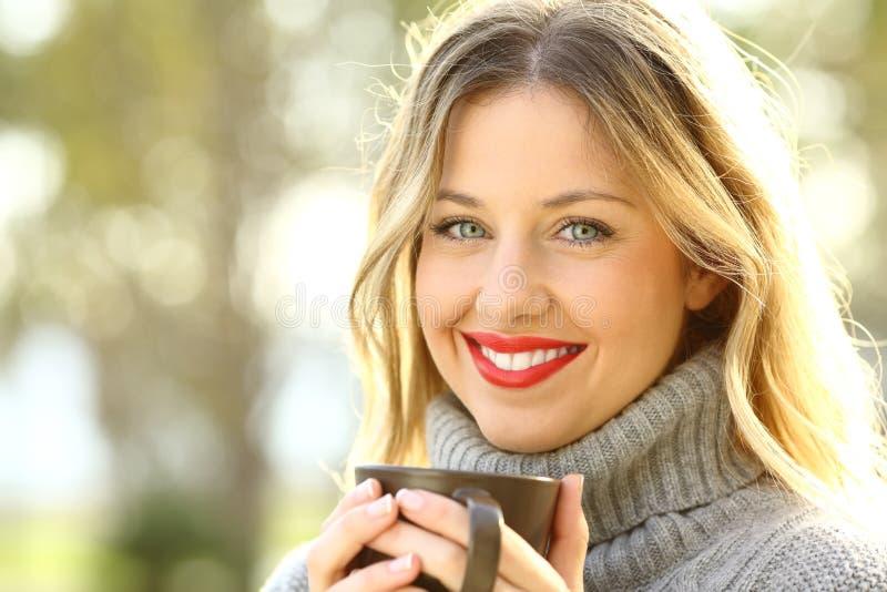 Stående av en lycklig dam som rymmer en kopp kaffe fotografering för bildbyråer