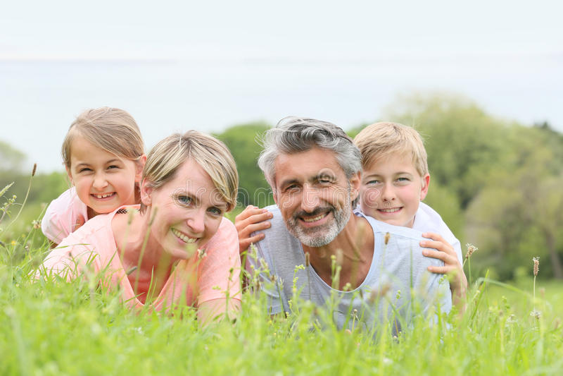 Stående av en lycklig familj som ligger i gräs arkivbild