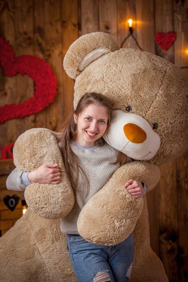 Stående av en lycklig flicka med en enorm björn arkivbilder
