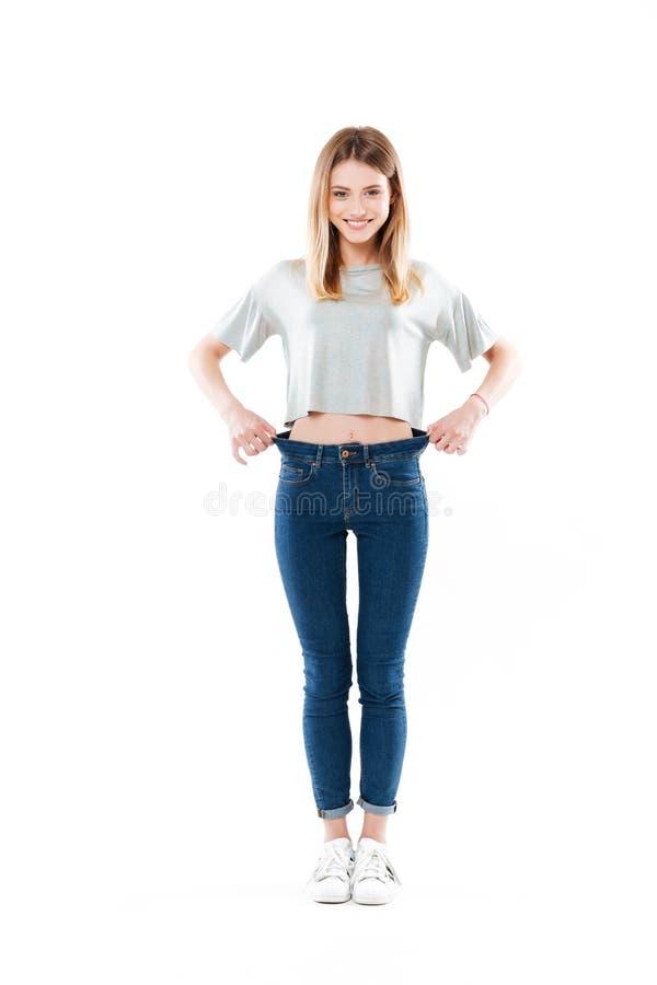 Stående av en lycklig glad flicka som visar hennes viktförlust arkivbild
