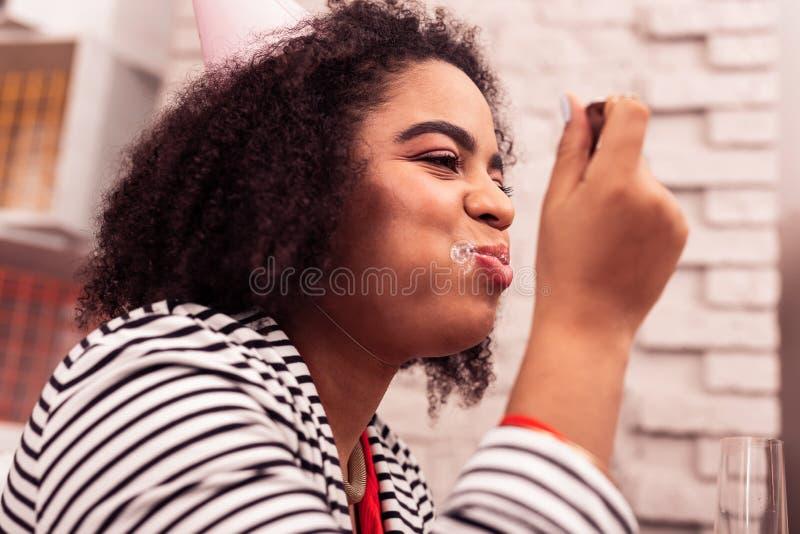Stående av en lycklig gladlynt kvinna, medan äta royaltyfria bilder