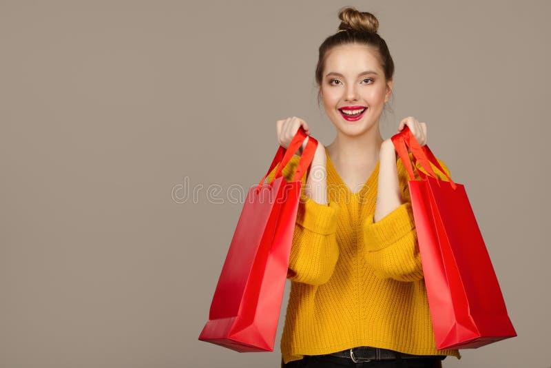 Stående av en lycklig gladlynt kvinna som rymmer röda shoppa påsar royaltyfria foton