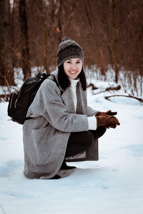 Stående av en lycklig härlig flicka med brunt hår i den iklädda vinterskogen en hipsterstil, livsstil royaltyfri foto