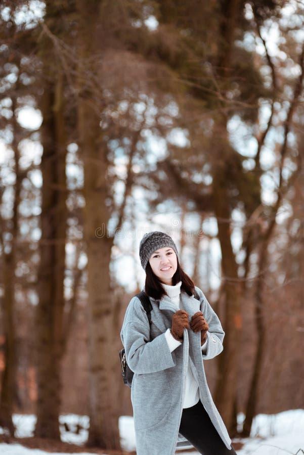Stående av en lycklig härlig flicka med brunt hår i den iklädda vinterskogen en hipsterstil, livsstil royaltyfri bild