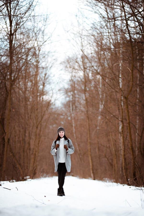 Stående av en lycklig härlig flicka med brunt hår i den iklädda vinterskogen en hipsterstil, livsstil fotografering för bildbyråer