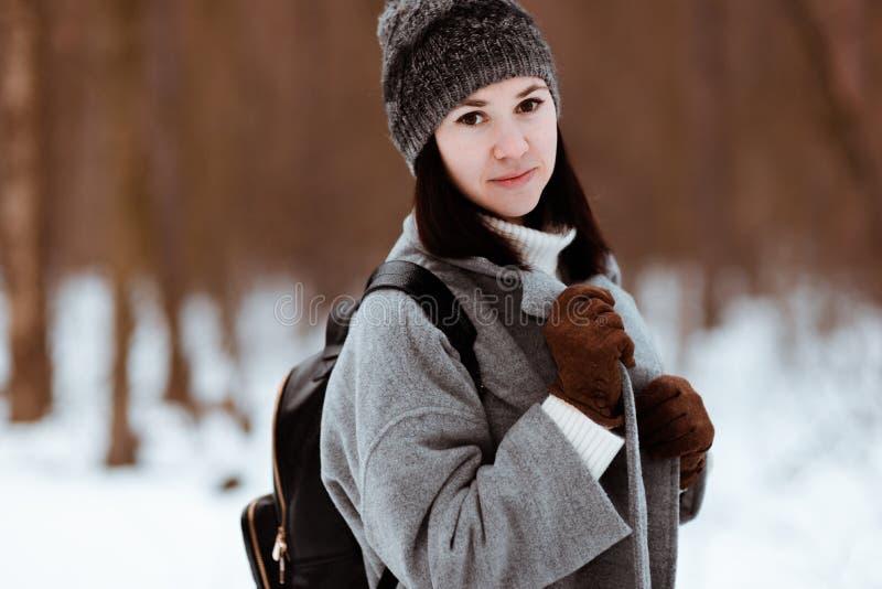 Stående av en lycklig härlig flicka med brunt hår i den iklädda vinterskogen en hipsterstil, livsstil royaltyfria foton