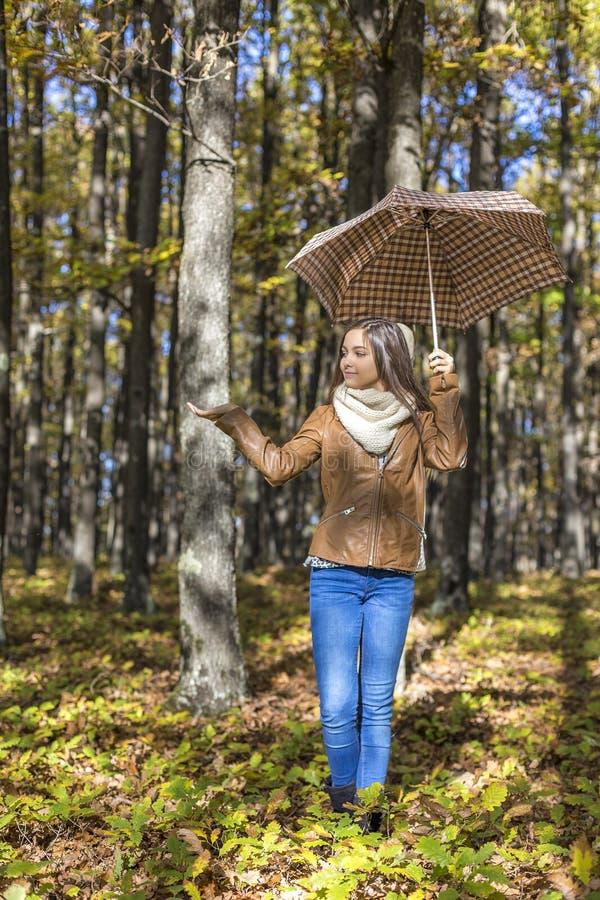 Stående av en lycklig härlig tonårs- flicka som rymmer ett paraply arkivbild