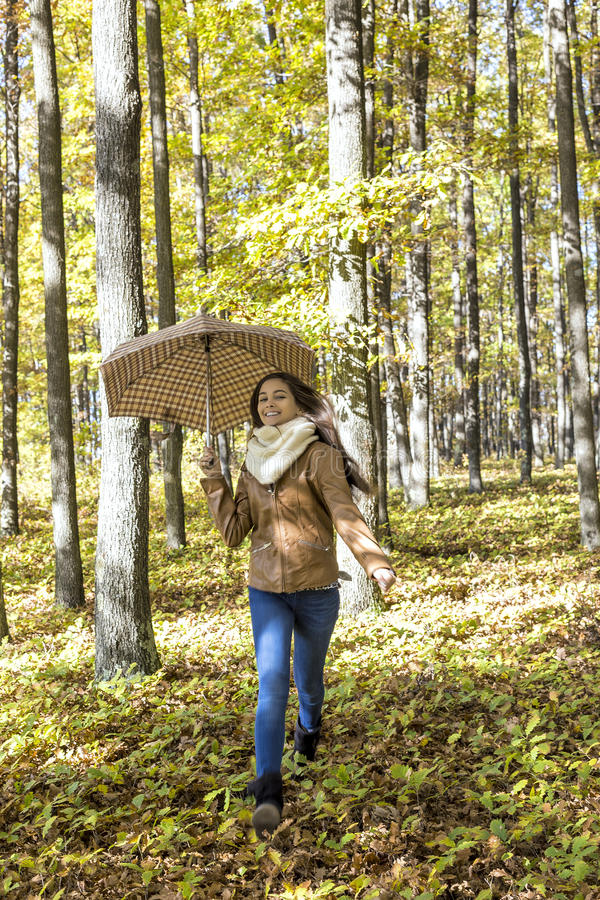 Stående av en lycklig härlig tonårs- flicka som rymmer ett paraply royaltyfria foton