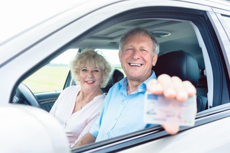 Stående av en lycklig hög man som visar hans körningslicens medan fotografering för bildbyråer