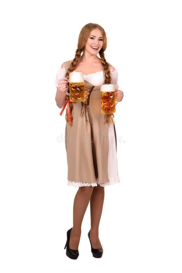Stående av en lycklig kvinna som bär den traditionella Oktoberfest dräkten med två ölexponeringsglas och innehavtecken Isolerat p arkivfoto