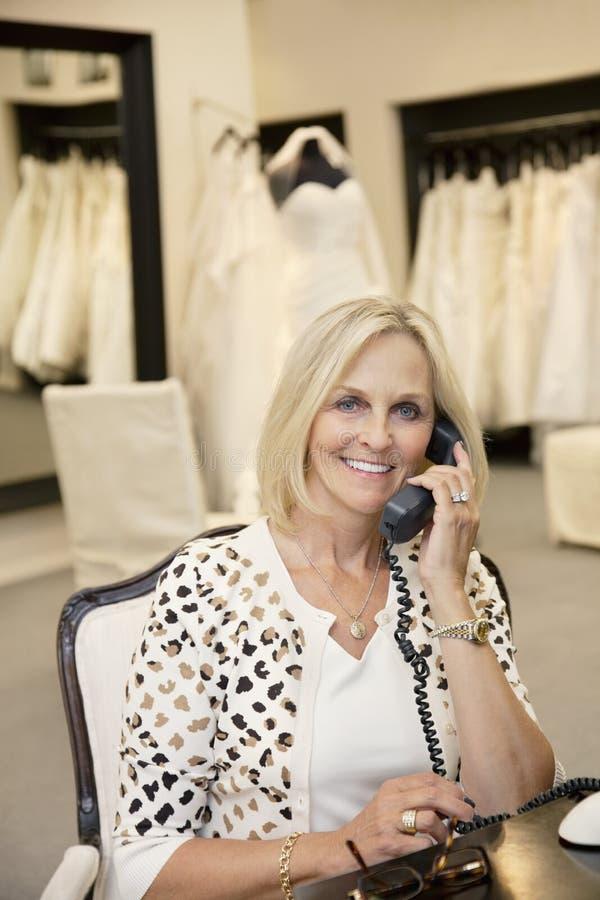 Stående av en lycklig kvinna som lyssnar till telefonmottagaren i brud- lager royaltyfri bild
