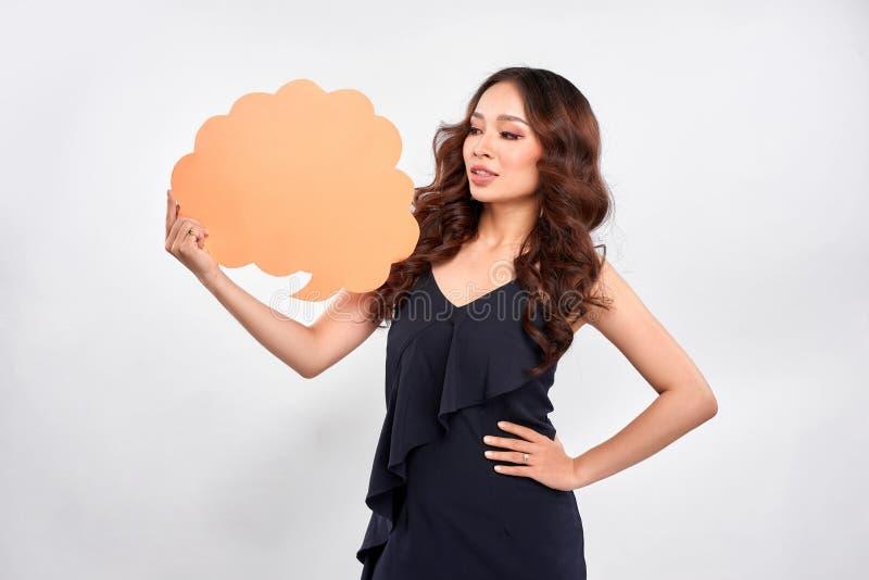 Stående av en lycklig kvinna som rymmer den tomma anförandebubblan över grå bakgrund arkivfoton