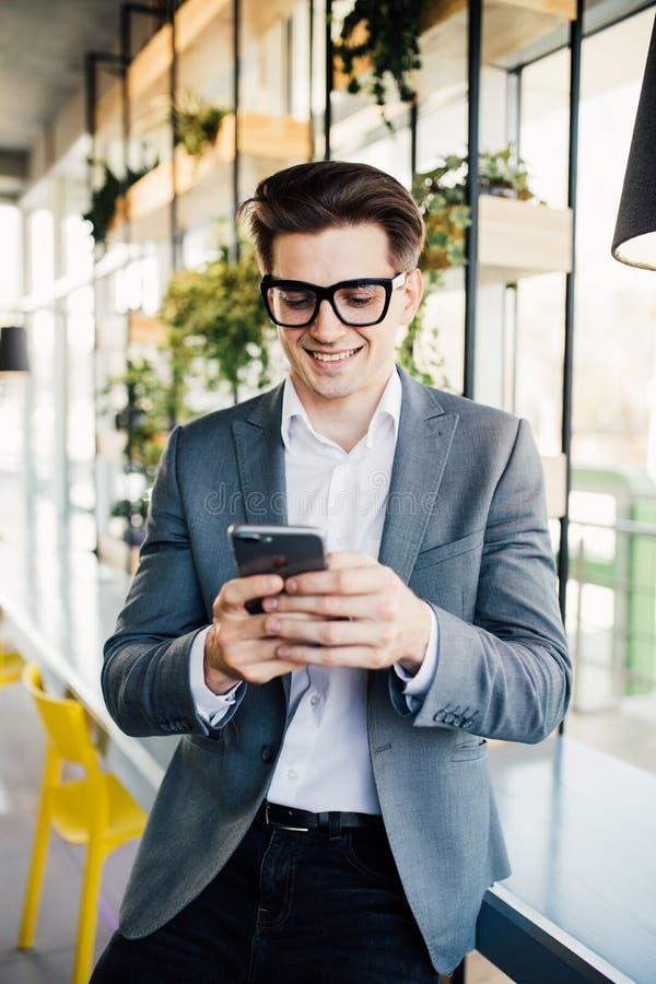 Stående av en lycklig le affärsman i glasögon genom att använda smartphonen, medan sitta på kontoret royaltyfri fotografi