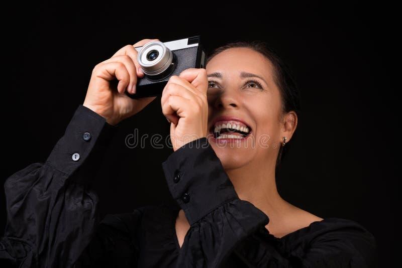 stående av en lycklig le kvinna som tar fotoet på en retro kamera över svart bakgrund royaltyfri fotografi