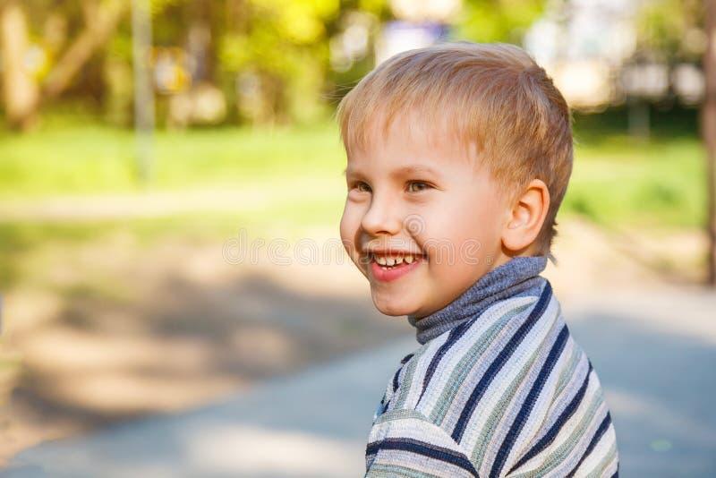 Stående av en lycklig le pojke som går i gatan royaltyfria foton