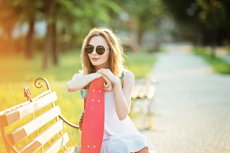 Stående av en lycklig le ung kvinna med en rosa skateboard royaltyfria bilder