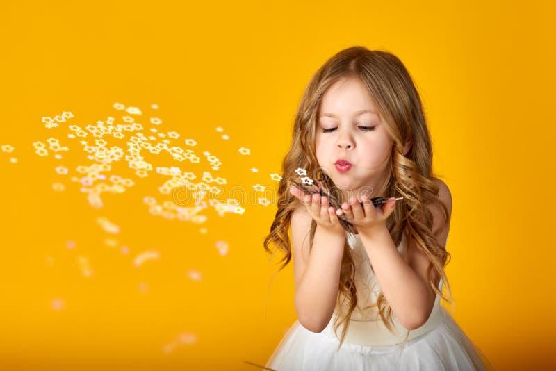Stående av en lycklig liten flicka som blåser av konfettier på en kulör bakgrund arkivfoto