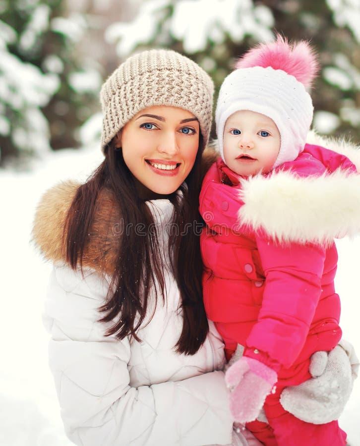 Stående av en lycklig moder med barnet utomhus i vintern arkivbilder