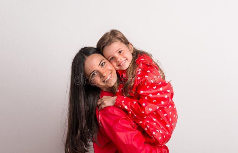 Stående av en lycklig moder som rymmer en liten flicka med den röda anoraken i studio royaltyfri fotografi