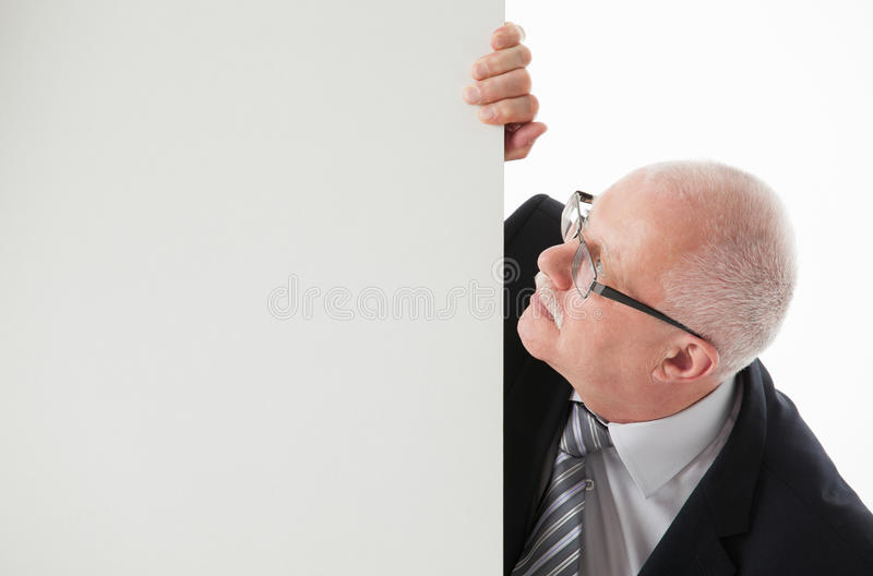 Stående av en lycklig mogen affärsman som rymmer det tomma vita brädet arkivfoto