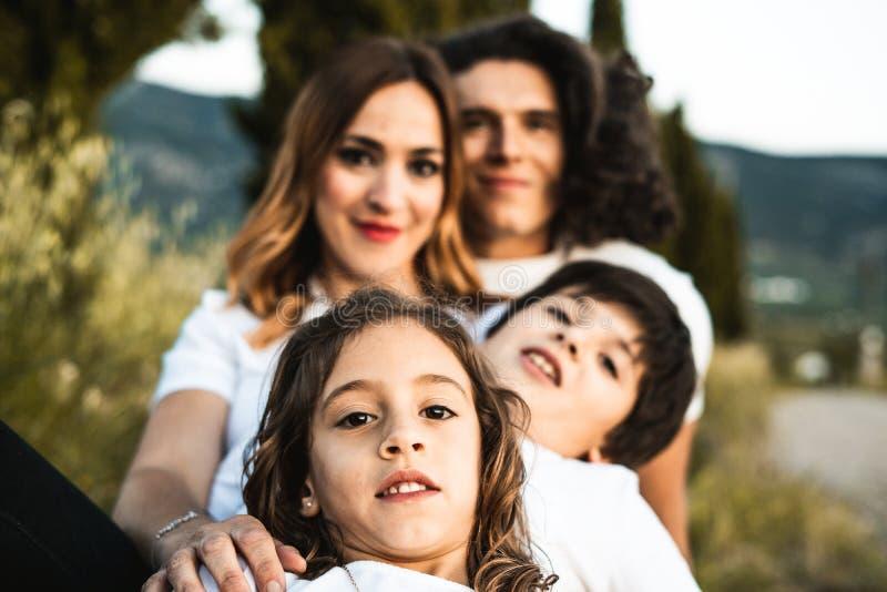 Stående av en lycklig och rolig ung familj utomhus arkivfoton
