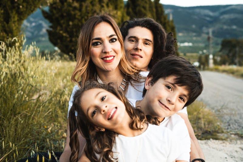 Stående av en lycklig och rolig ung familj utomhus arkivfoto