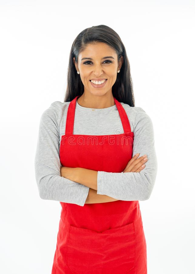 Stående av en lycklig stolt härlig latinsk kvinna som bär ett rött förkläde som lär att laga mat framställning av tummen upp gest royaltyfria foton