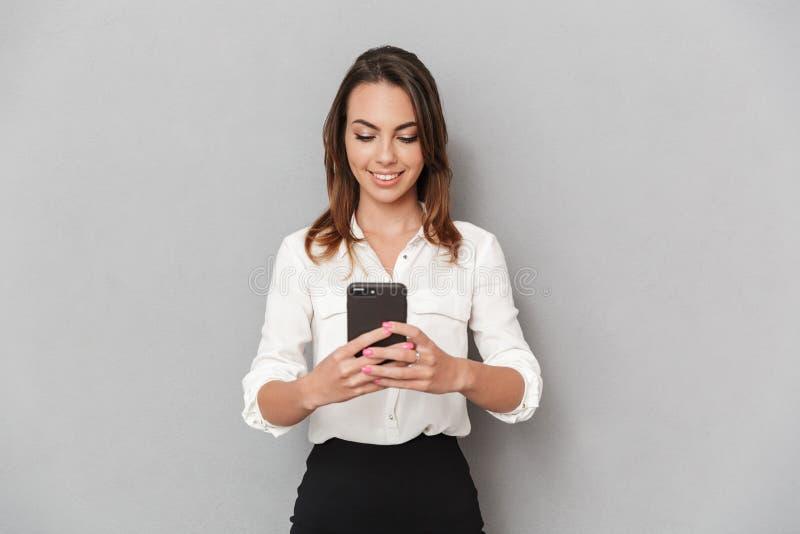 Stående av en lycklig ung affärskvinna som använder mobiltelefonen fotografering för bildbyråer