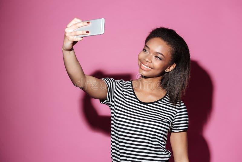 Stående av en lycklig ung afrikansk kvinna som tar selfie royaltyfria foton
