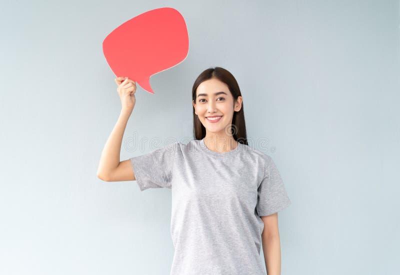 Stående av en lycklig ung asiatisk kvinna, medan rymma upp anförandebubblasymboler över grå bakgrund fotografering för bildbyråer