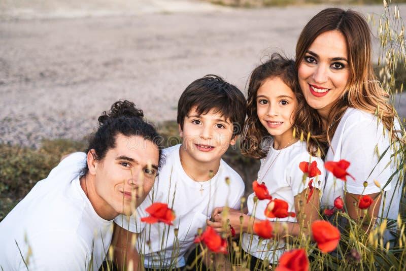 Stående av en lycklig ung familj som ler och se kameran på yttersidan fotografering för bildbyråer
