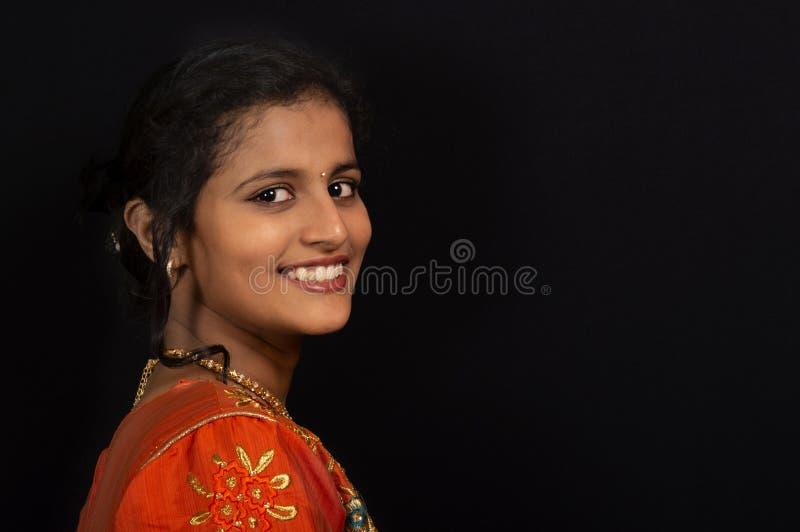 Stående av en lycklig ung indisk flicka som ler på svart bakgrund arkivfoto