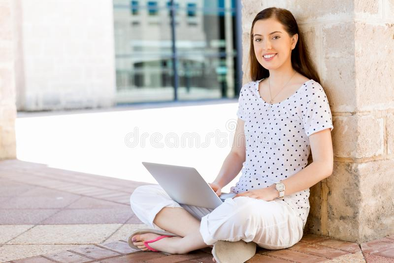 Stående av en lycklig ung kvinna som utomhus använder bärbar datordatoren royaltyfria foton