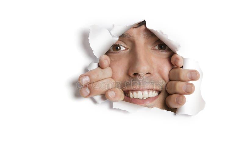 Stående av en lycklig ung latinamerikansk man som kikar från det rev sönder pappers- hålet arkivbild