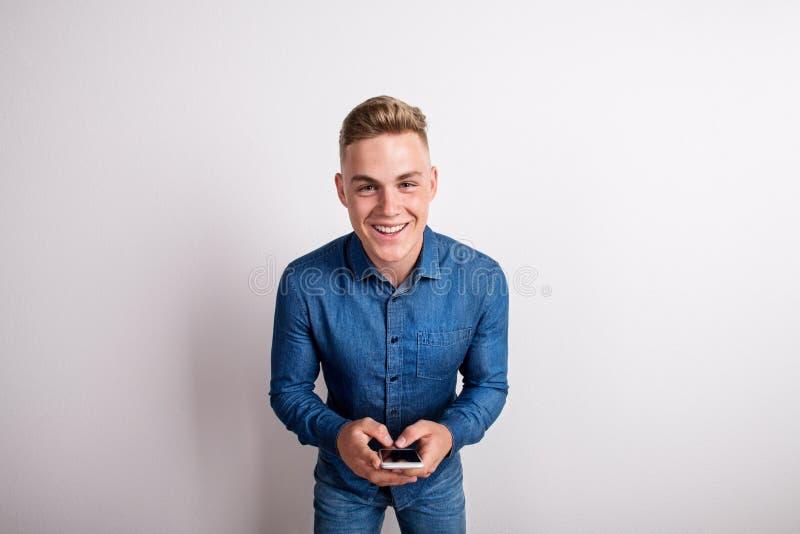 Stående av en lycklig ung man i en studio, hållande smartphone arkivbilder