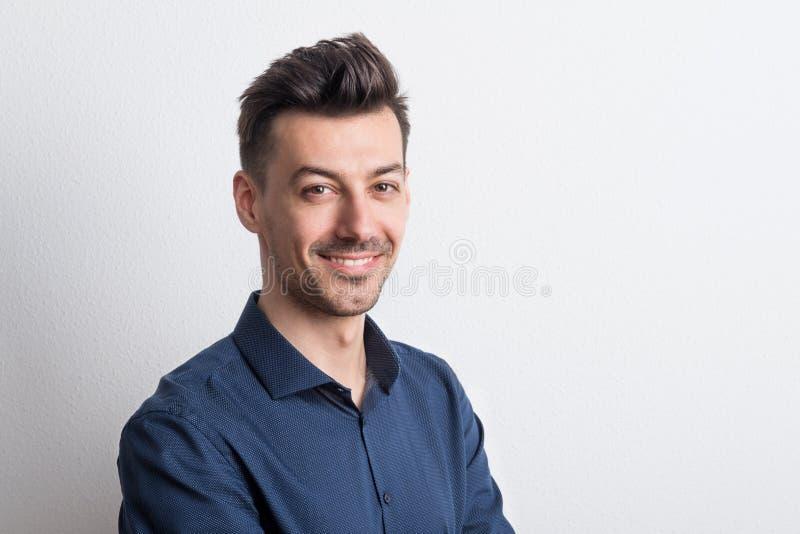 Stående av en lycklig ung man i en studio kopiera avstånd arkivfoto