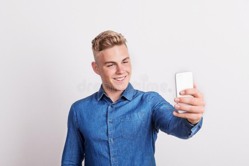 Stående av en lycklig ung man med en smartphone i en studio som tar selfie arkivfoton