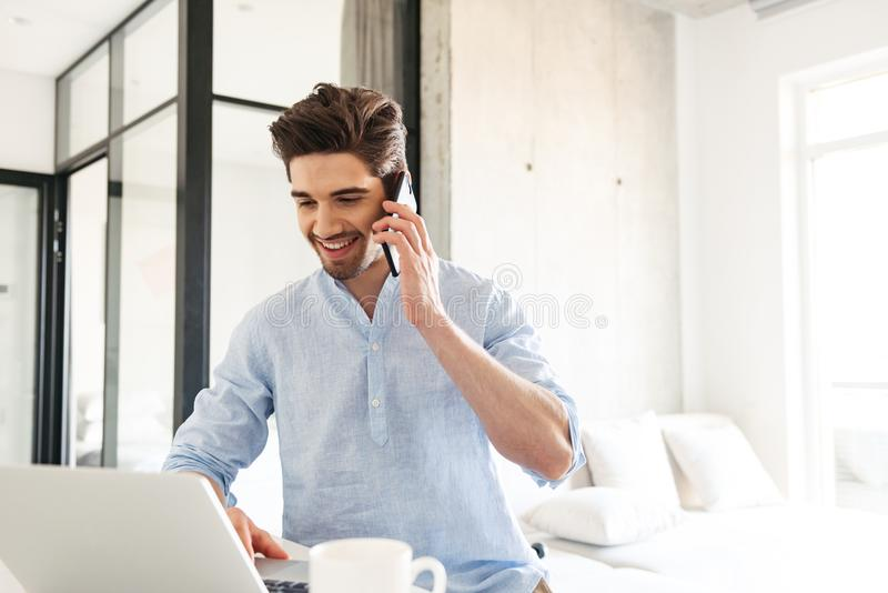 Stående av en lycklig ung man som använder bärbar datordatoren arkivbild