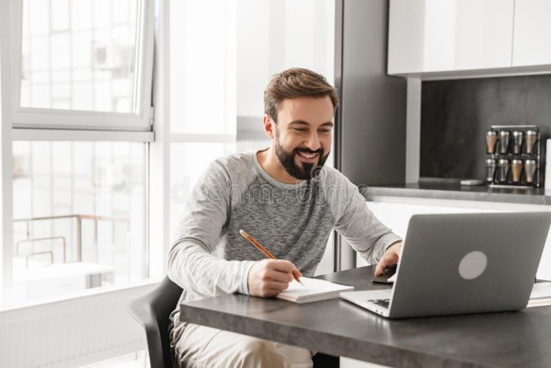 Stående av en lycklig ung man som arbetar på bärbara datorn arkivfoton