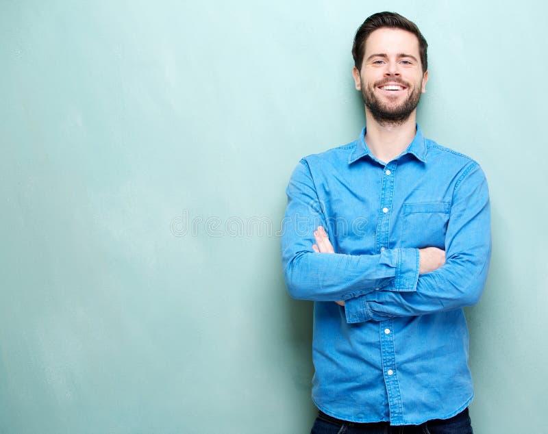 Stående av en lycklig ung man som ler med korsade armar royaltyfria bilder