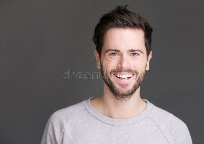 Stående av en lycklig ung man som ler på grå bakgrund royaltyfria bilder