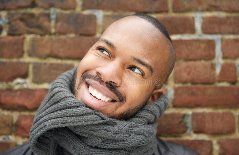 Stående av en lycklig ung man som utomhus ler arkivfoton