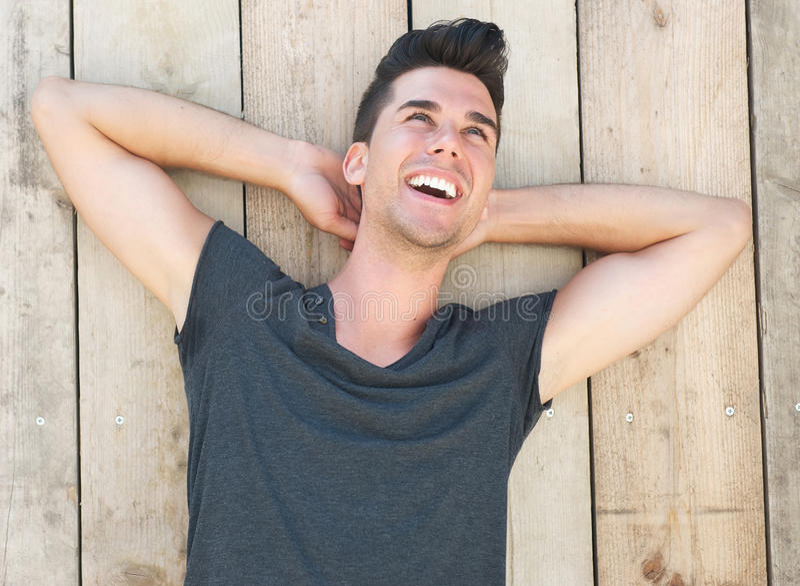 Stående av en lycklig ung manlig modell som utomhus skrattar arkivfoton