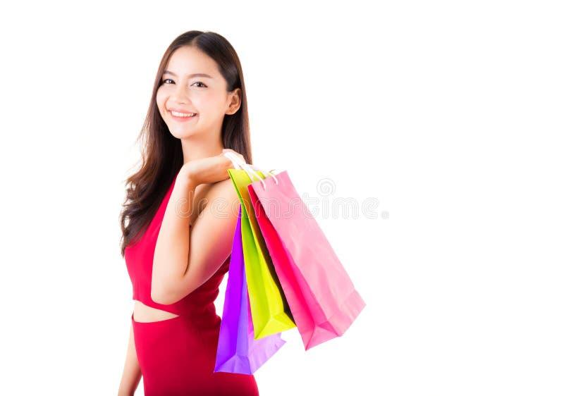 Stående av en lycklig upphetsad asiatisk kvinna i rött klänninganseende och färgrika isolerade shoppingpåsar för innehav med lyck royaltyfri fotografi