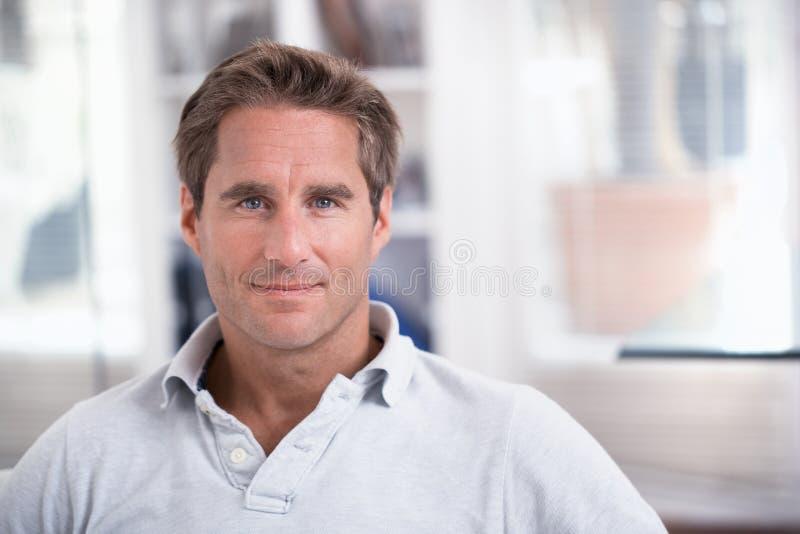 Stående av en man bara, inomhus arkivfoton
