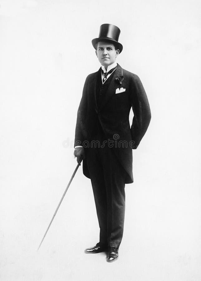 Stående av en man i bästa en hatt- och morgondräkt som rymmer en rotting (alla visade personer inte är längre uppehälle, och inge arkivfoto