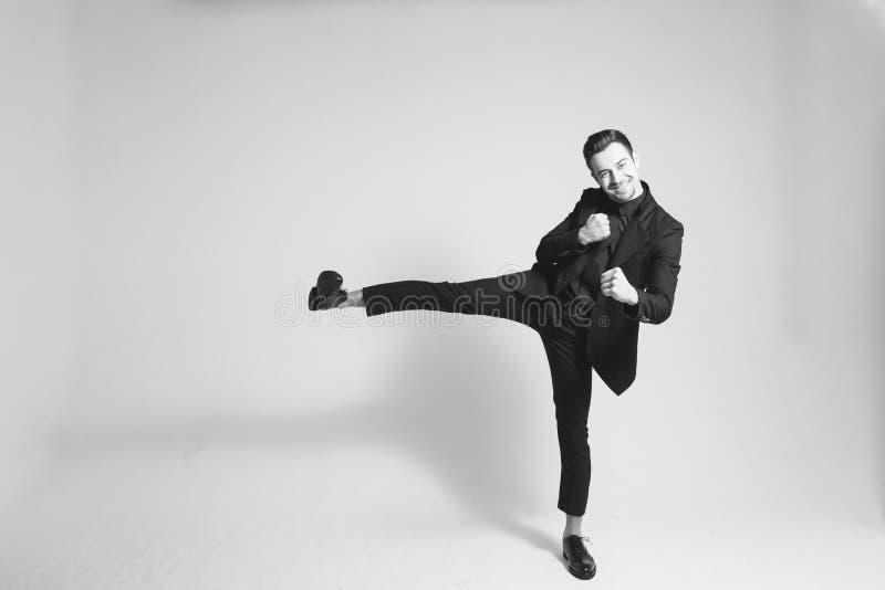 Stående av en man i ett svart dräktanseende på en fot fotografering för bildbyråer
