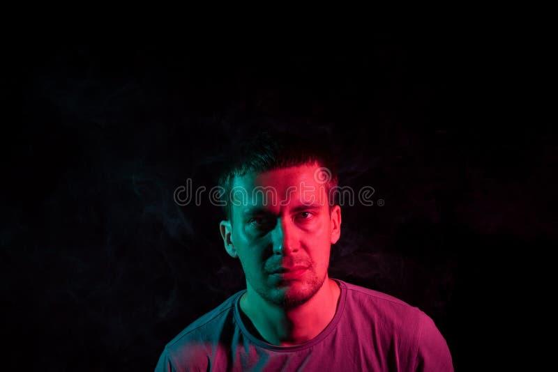Stående av en man i profilframsida på en svart isolerad bakgrund med en känsla av sorgsenhet och ensamhet, runt om huvudet ett mo royaltyfri fotografi