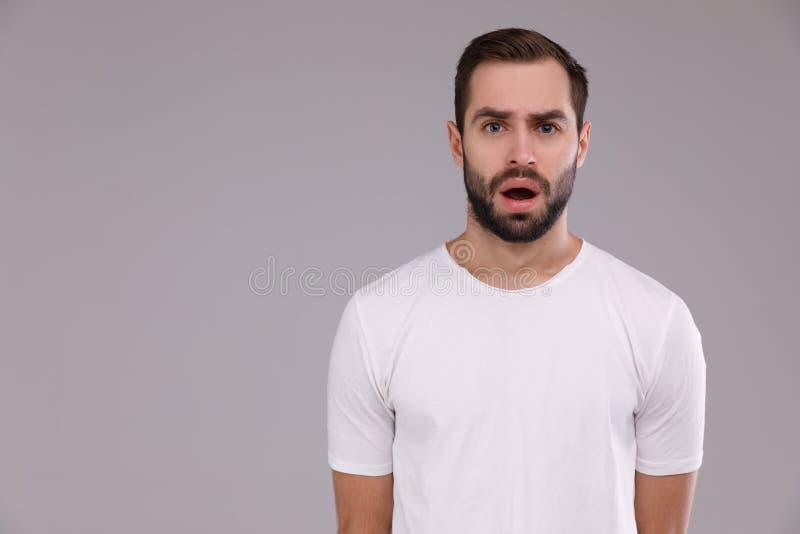 Stående av en man i en vit T-tröja på en grå bakgrund royaltyfria foton
