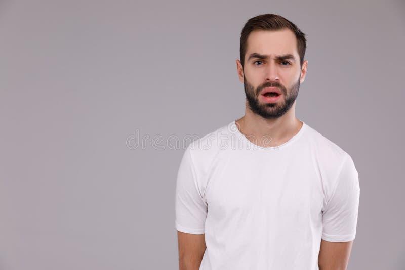 Stående av en man i en vit T-tröja på en grå bakgrund arkivbild